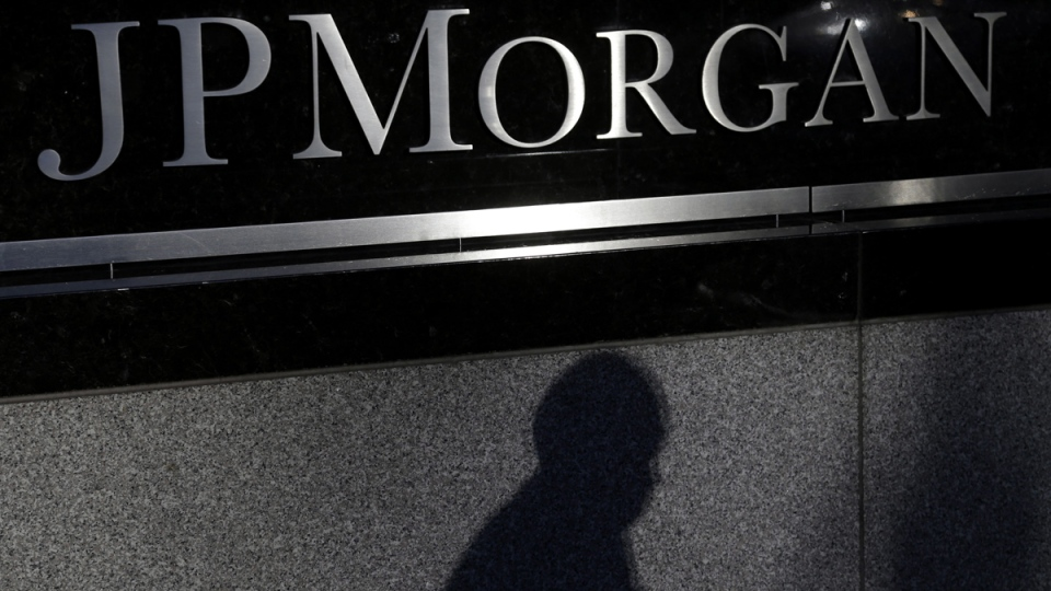 The shadow of a pedestrian is cast under a sign in front of JPMorgan Chase & Co. headquarters in New York, Nov. 19, 2013. (AP / Seth Wenig)