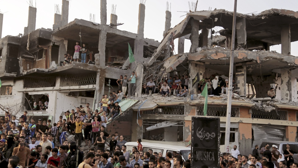 Palestinians attend a victory rally organized by masked militant of Izzedine al-Qassam Brigades, military wing of Hamas, at the debris of destroyed houses in Shijaiyah, neighborhood of Gaza City, in the northern Gaza Strip, Wednesday, Aug. 27, 2014. (AP / Adel Hana)