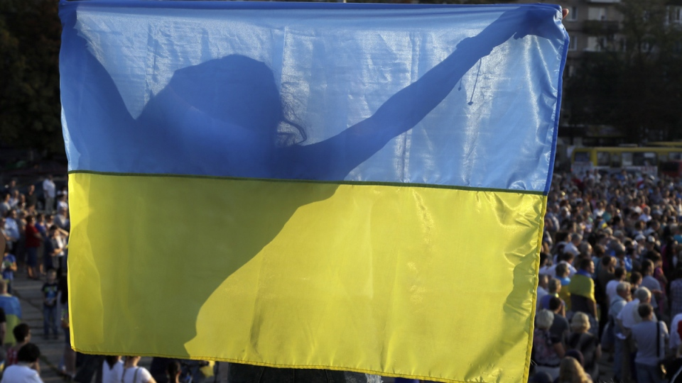 A girl waves a Ukrainian flag during an anti-war meeting in the town of Mariupol, eastern Ukraine, Thursday, Aug. 28, 2014. (AP / Sergei Grits)