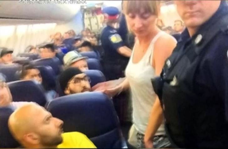 Milana Muzikante of Vaughan, Ont. is escorted off a plane after allegedly disrupting a Cuba-bound plane and forcing it to return to Toronto. (Victoria Rivera)