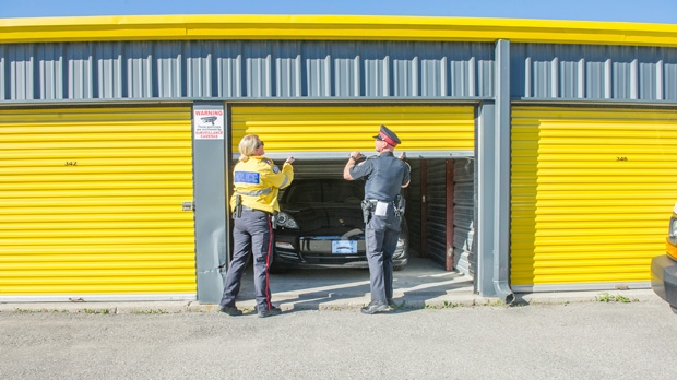 Officers execute a search warrant for a Porsche Panamera on Thursday, Aug. 28, 2014. Police allege the vehicle is one of dozens of stolen luxury vehicles recovered across the GTA and Niagara regions. (Police handout)