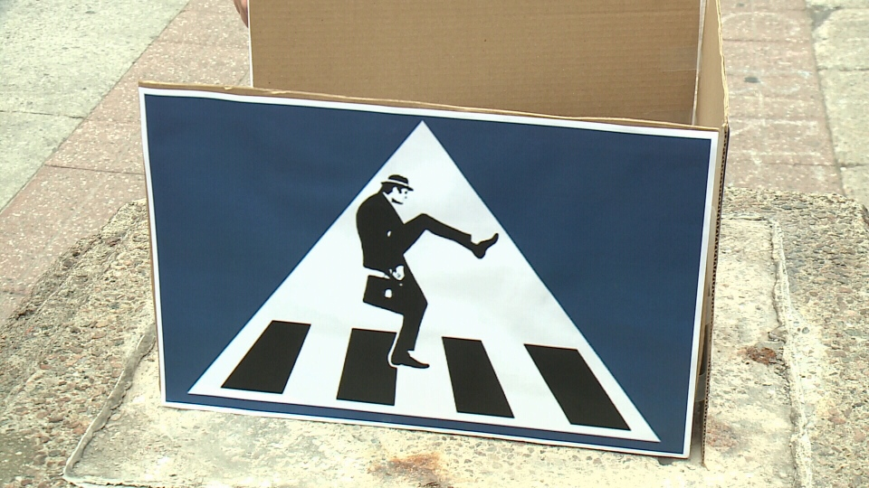 "Crossing signs like this one are encouraging people to use their best ""silly walk"" on Ottawa's Sparks Street, Aug. 28, 2014"