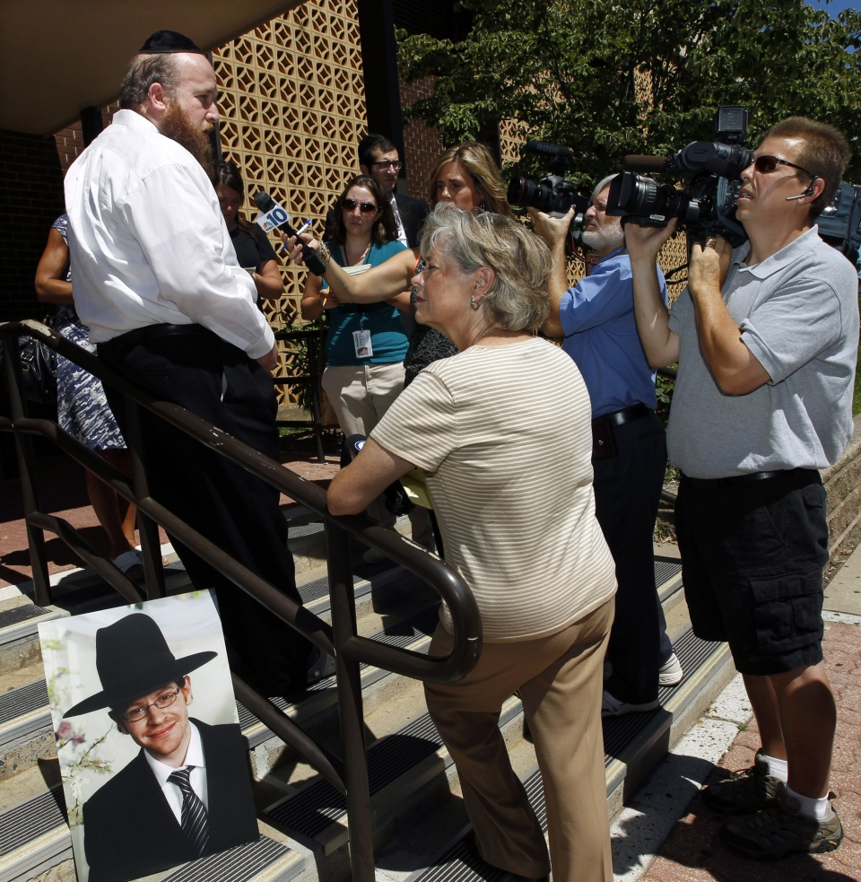 A photograph of Aharon Sofer, left, sits on the steps as family friend, Yaakov Wenger, left, speaks to reporters in Lakewood, N.J. on Thursday, Aug. 28, 2014. (AP / Mel Evans)
