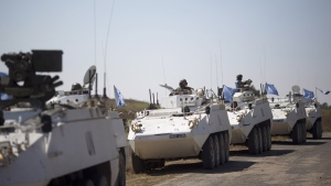 Armoured vehicles from the U.N. peacekeepers of the United Nations Disengagement Observer Force, also known as UNDOF wait to cross from the Israeli controlled Golan Heights to Syria, Thursday, Aug. 28, 2014. (AP / Ariel Schalit)