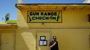 An employee smokes outside of an office for the Last Stop outdoor shooting range, in White Hills, Ariz., Wednesday, Aug. 27, 2014. (AP / John Locher)