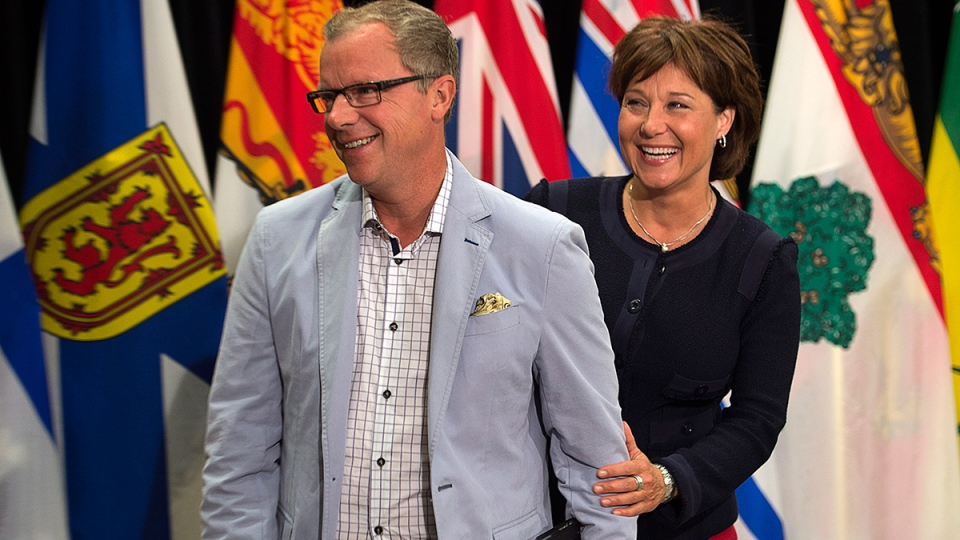 Saskatchewan Premier Brad Wall, left and British Columbia Premier Christy Clark share a light moment after announcing the lowering of trade barriers involving wine and some spirits between the two provinces at the annual Council of the Federation meeting in Charlottetown on Friday, Aug. 29, 2014. (Andrew Vaughan / THE CANADIAN PRESS)
