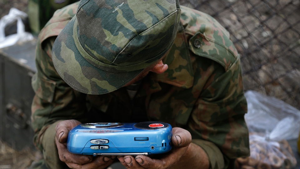 A pro-Russian rebel listens to the news on a transistor radio in the town of Novoazovsk, in eastern Ukraine, Friday, Aug. 29, 2014. (AP / Sergei Grits)