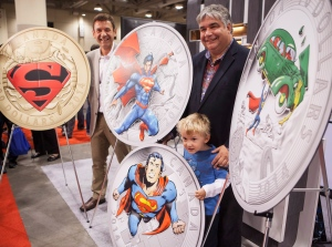 Vice President of Marketing at the Royal Canadian Mint Patrick Hadsipantelis, left, and Leader of the Government in the House of Commons Peter Van Loan and his son John unveil four new collector coins featuring Superman on Friday, August 29, 2014. (Jesse Johnston / THE CANADIAN PRESS)