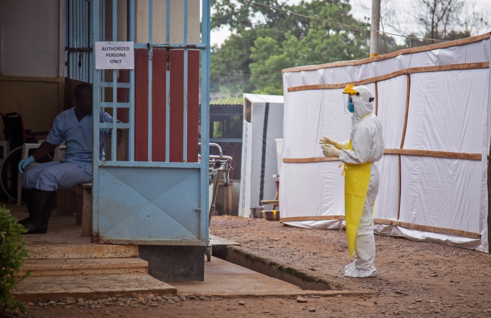 In this photo taken on Tuesday, Aug 12, 2014, a healthcare worker, right, wears protective gear against the Ebola virus before he enters the Ebola isolation ward at Kenema Government Hospital, in Kenema, the Eastern Province around 300km, from the capital city of Freetown in Sierra Leone. (AP/ Michael Duff)