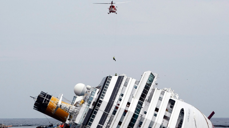 An Italian firefighter is lowered from an helicopter onto the grounded cruise ship Costa Concordia off the Tuscan island of Giglio, Italy, Tuesday, Jan. 31, 2012.