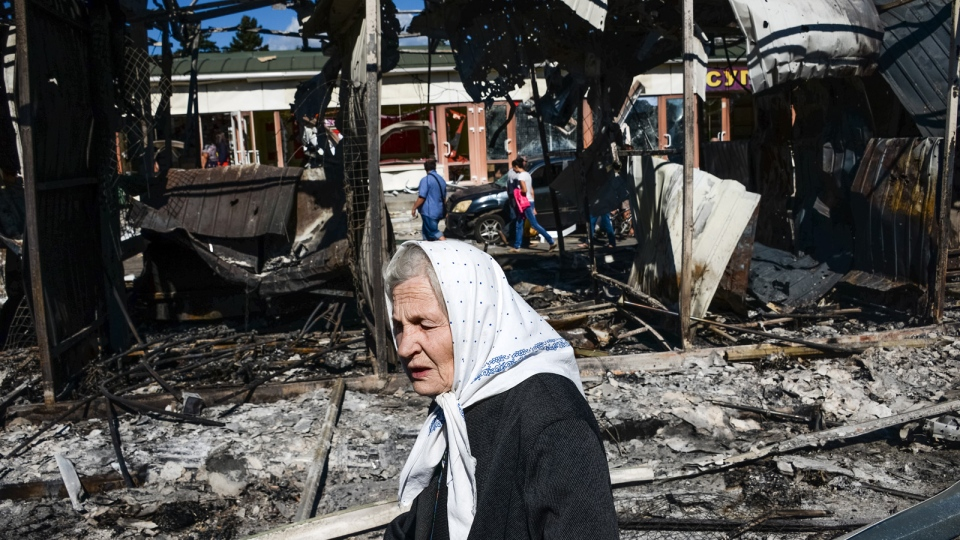 A woman passes by shops burned by shelling near the train station in Donetsk, Ukraine, Saturday, Aug. 30, 2014. (AP / Mstyslav Chernov)
