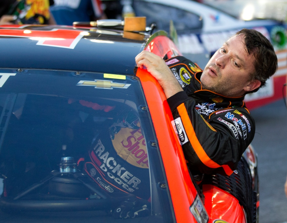 Sprint Cup Series driver Tony Stewart (14) climbs out of his car after qualifying for Sunday's Oral B USA 500 NASCAR auto race at Atlanta Motor Speedway in Hampton, Ga. on Friday, Aug. 29, 2014. (AP / John Bazemore)