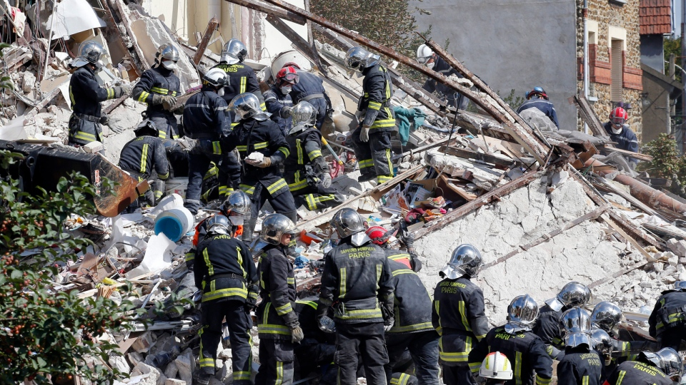 French firemen search in the rubble of a building after an explosion collapsed it, in Rosny-sous-Bois, outside Paris, Sunday, Aug. 31, 2014. (AP / Christophe Ena)