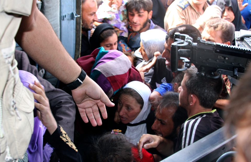 Iraqi Shiite Turkmens, mostly women and children, try to board an Iraqi Army helicopter aid flight bringing in supplies to Amirli. (AP Photo)