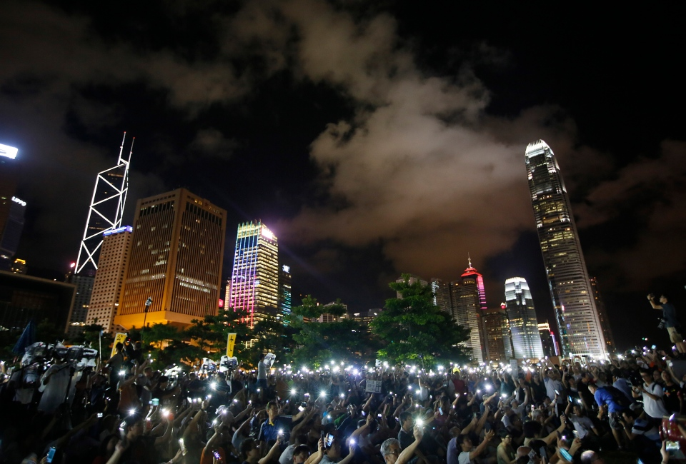 Protesters wave their mobile phones during a rally after China's legislature has ruled out open nominations in elections for Hong Kong's leader in Hong Kong on Sunday, Aug. 31, 2014. (AP / Vincent Yu)