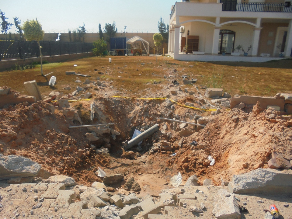 In this photo taken during a tour offered to onlookers and journalists by the Dawn of Libya militia on Sunday, Aug. 31, 2014, damage is seen in the front yard of a building at the U.S. Embassy compound in Tripoli, Libya, after weeks of violence between rival militias over control of the capital. (AP Photo)