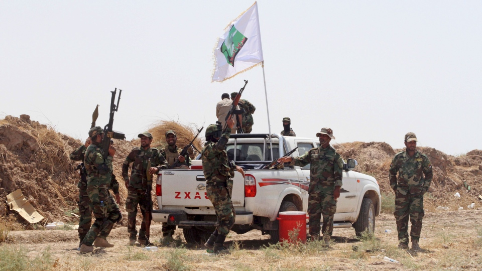 Iraqi security forces and Shiite militiamen chant anti-terrorism slogans after breaking the siege on 15,000 Shiite Turkmens stranded in the farming community town of Amirli, following U.S. airstrikes against Sunni Islamic State group positions, 105 miles (170 kilometers) north of Baghdad, Sunday, Aug. 31, 2014. (AP Photo)