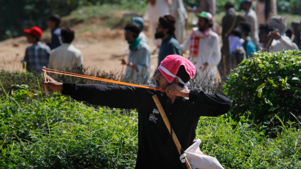 A Pakistani protester uses slingshot to shoot a stone towards police during a clash near the house of Prime Minister Nawaz Sharif in Islamabad, Pakistan Sunday, Aug. 31, 2014. (AP / Anjum Naveed)