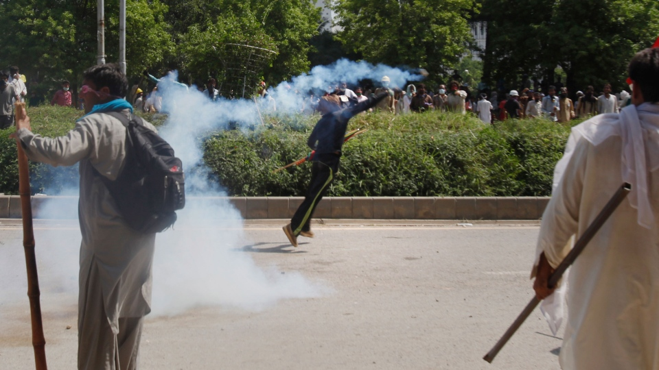 A protester hurls back a tear gas shell fired by police to disperse them during a clash near the house of Prime Minister Nawaz Sharif in Islamabad, Pakistan Sunday, Aug. 31, 2014. (AP / Anjum Naveed)