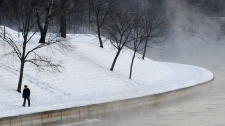 A man walks beside the Neris river in the Vilnius, Lithuania, Wednesday, Feb. 1, 2012, as morning temperatures plummeted to -23 Celsius. (AP Photo/Mindaugas Kulbis)