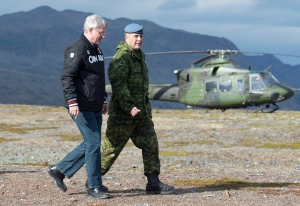 Prime Minister Stephen Harper (left) speaks with Commander Joint Task Force North Brig.Gen. Greg Loos as they make there way to speak to troops on Baffin Island near York Sound, Nunavut, Tuesday, August 26, 2014. (Adrian Wyld / THE CANADIAN PRESS)