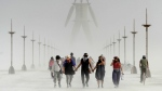 Burning Man participants walk through dust at the annual Burning Man event on the Black Rock Desert of Gerlach, Nev., on Friday, Aug. 29, 2014. (AP Photo/The Reno Gazette-Journal, Andy Barron)