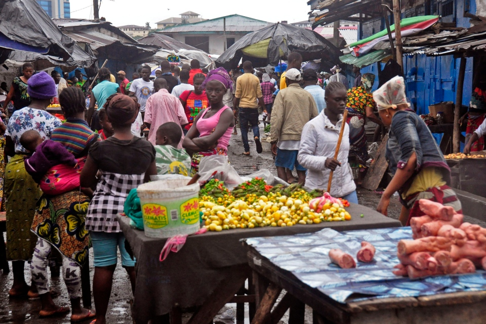 People buy foods at a local market after Liberian authorities reopened the West Point slum where tens of thousands of people were barricaded amid the country's Ebola outbreak in Monrovia, Liberia, Saturday, Aug. 30, 2014. (AP / Abbas Dulleh)
