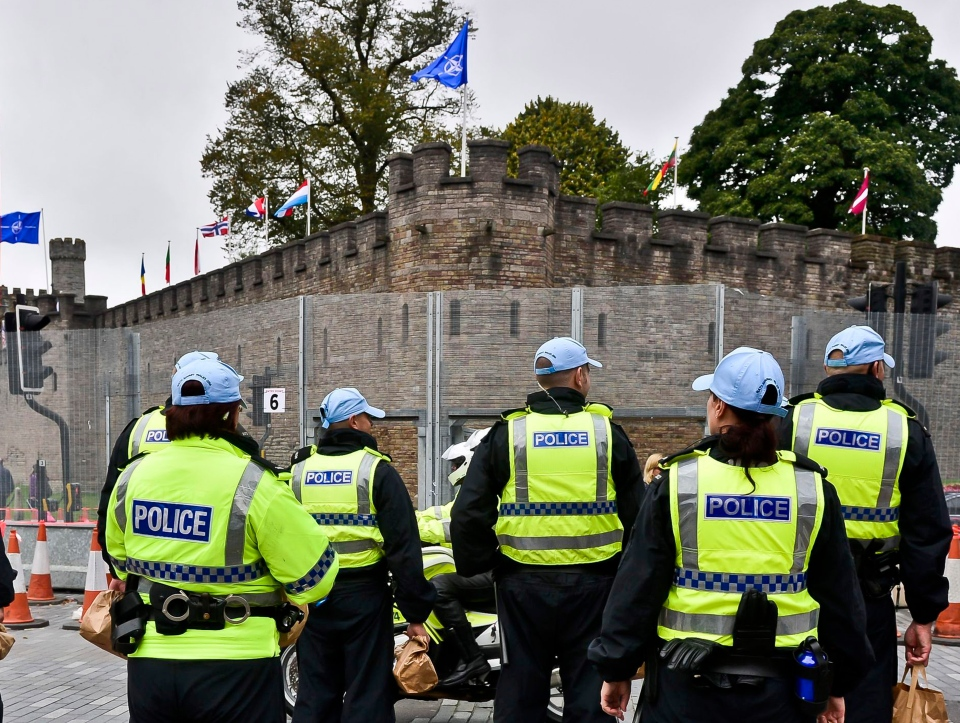 A NATO flag and flags of many nations fly from the ramparts of Cardiff Castle as a heavy police presence secures the area outside security fencing surrounding the castle ahead of the upcoming NATO summit in Newport, Wales, Monday Sept. 1, 2014. (AP / Ben Birchall)