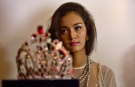 May Myat Noe, Myanmar's first international beauty queen, winner of 2014 Miss Asia Pacific World sits in the background of $100,000 worth crown, during a press conference in Yangon, Myanmar Tuesday, Sept 2, 2014.(AP Photo/Gemunu Amarasinghe)