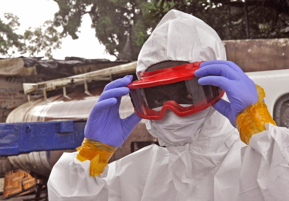 A Liberian health worker prepare his Ebola protective gear before removing the body of a man that they believe died from the Ebola virus in Monrovia, Liberia, Friday, Aug. 29, 2014. (AP Photo/Abbas Dulleh)