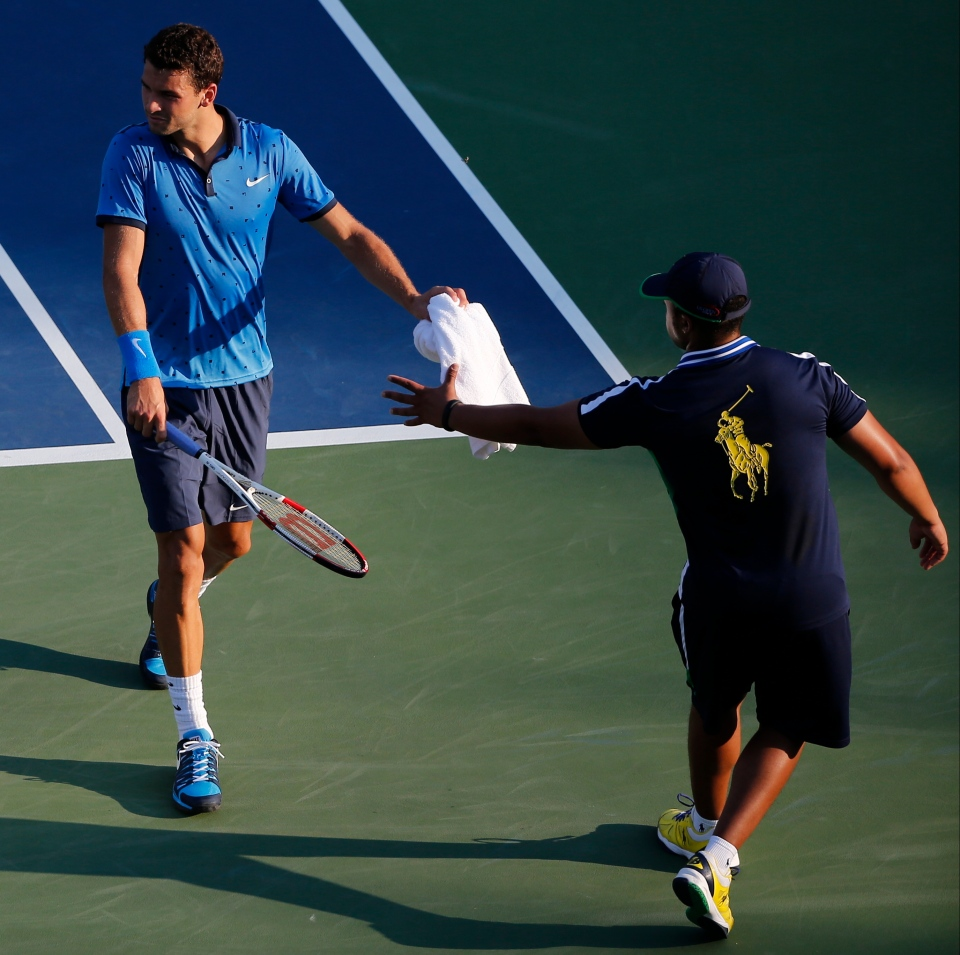 Grigor Dimitrov, of Bulgaria, hands a towel back to a ball person after wiping sweat from his face during the second round of the 2014 U.S. Open tennis tournament on Wednesday, Aug. 27, 2014, in New York. (AP / Elise Amendola)