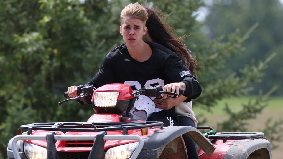 Justin Bieber and Selena Gomez ride an ATV in the Township of Perth East near his hometown of Stratford, Ont. (etalk)