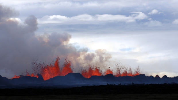A plume of smoke rises from the lava eruption on Holuhraun, northwest of the Dyngjujoekull glacier in Iceland, Monday, Sept. 1, 2014. <br><br> Lava fountains dance along a lengthy volcanic fissure near Iceland&#39;s subglacial Bardarbunga volcano. The alert warning for the area surrounding Iceland&#39;s Bardarbunga volcano remained at orange on Tuesday, indicating that it is showing increased unrest with greater potential for an explosive eruption. (AP / Eggert Johannesson)