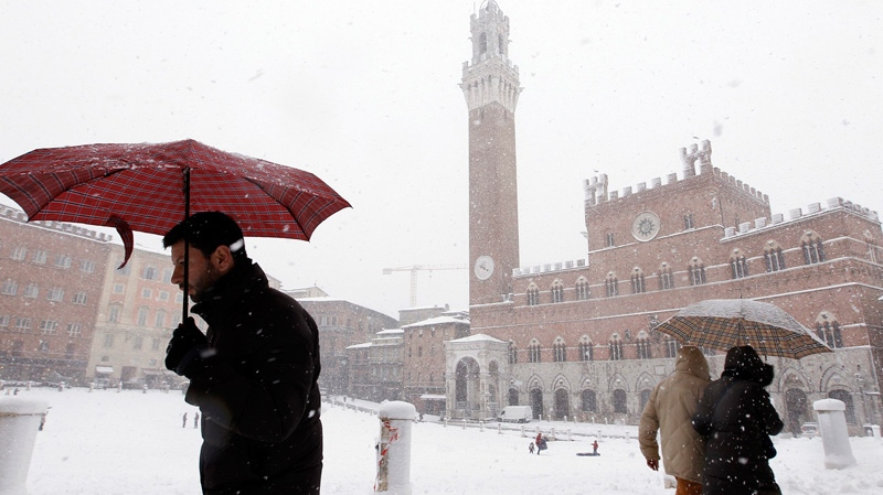 People walk through the historic center of Siena, central Italy, as snowfalls have been battering the country, Wednesday, Feb. 1, 2012. (AP / Paolo Lazzeroni)