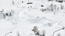 Kosovo Albanian men stroll near the damn of the artificial lake of Badovac, Wednesday, Feb. 1, 2012. (AP / Visar Kryeziu)