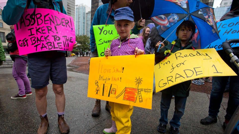 Cleo Petric-Neighbour, left, and her friend Milan Gill, both 6-years-old and entering grade 1 at Lord Roberts Elementary School, hold signs while attending a rally to show opposition to the teachers' strike in Vancouver, on Tuesday, Sept. 2, 2014. (Darryl Dyck / THE CANADIAN PRESS)