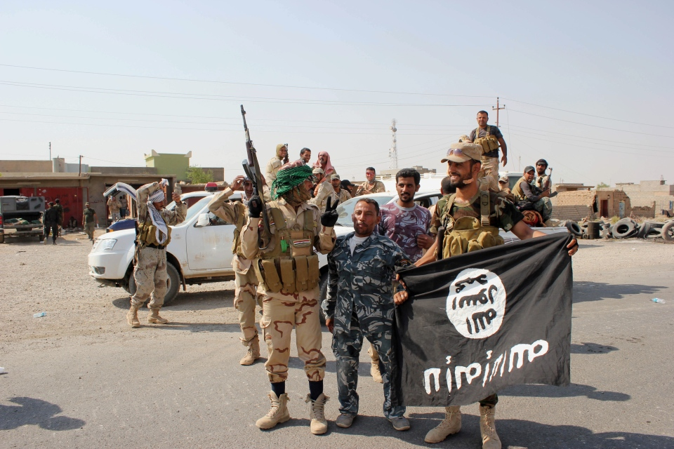 Shiite militiamen hold the flag of the Islamic State group they captured, during an operation outside Amirli, north of Baghdad, Iraq, on Monday, Sept. 1, 2014. (AP Photo)