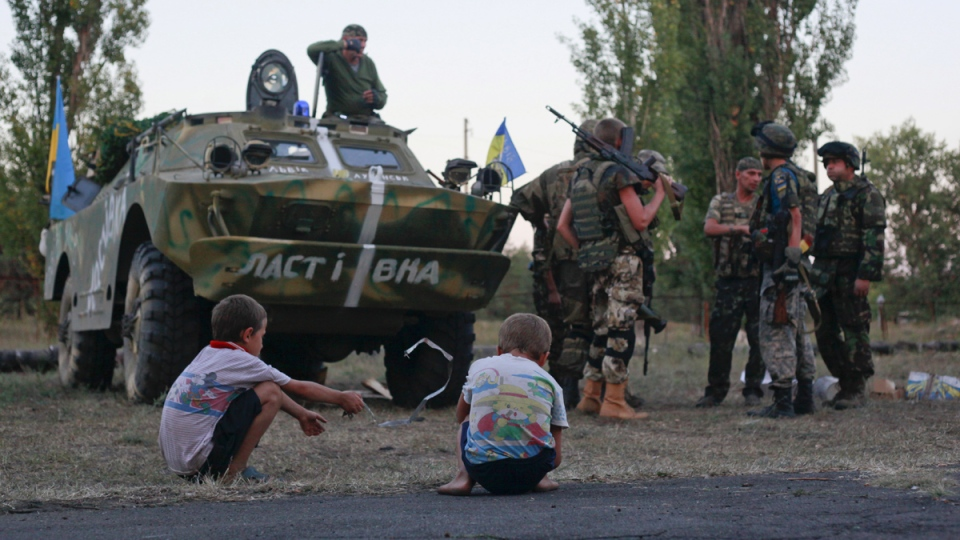 Children watch as the Ukrainian soldiers talk to each other in the small town of Shchastya in eastern Ukraine Wednesday, Sept. 3, 2014. (AP / Petro Zadorozhnyy)