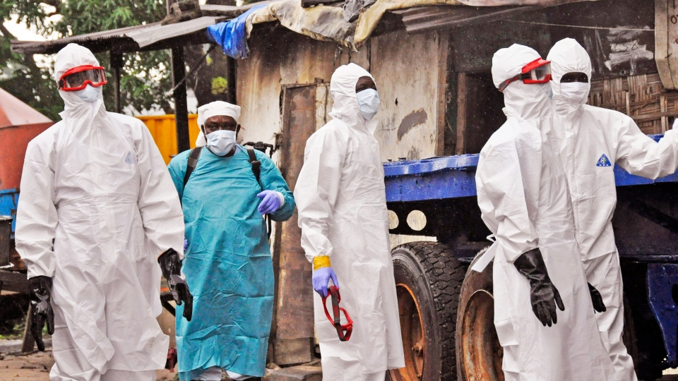 Liberian health workers outside a home of a man that they believed died from the Ebola virus in Monrovia, Liberia, Friday, Aug. 29, 2014. (AP / Abbas Dulleh)