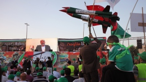 A celebrator carries a rocket decoy as Khaled Mashaal, leader of the Palestinian organization Hamas, speaks to the crowds via live broadcast during a celebration by the Muslim Brotherhood movement to declare victory of Gaza and Hamas against Israel, in Amman, Jordan, Friday, Aug. 29, 2014. (AP / Mohammad Hannon)