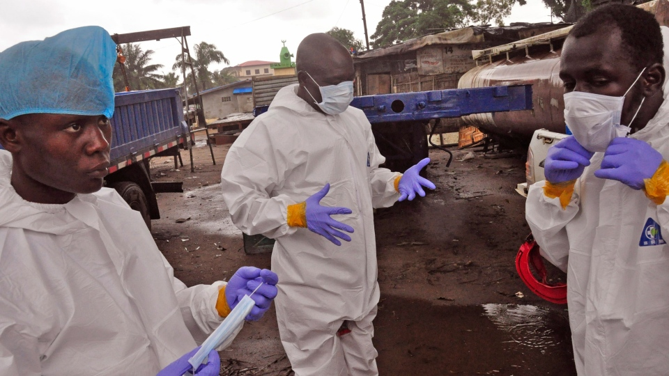 Liberian health worker prepare their Ebola protective gear before removing the body of a man that they believe died from the Ebola virus in Monrovia, Liberia, Friday, Aug. 29, 2014. (AP / Abbas Dulleh)