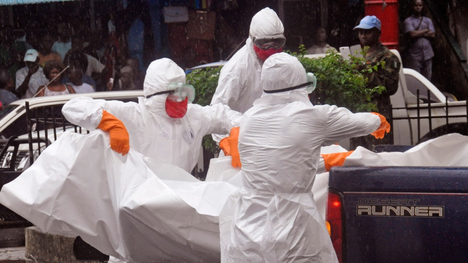 Health workers load the body of an amputee suspected of dying from the Ebola virus during the rain on the back of a truck, in a busy street in Monrovia, Liberia, Tuesday, Sept. 2, 2014. (AP / Abbas Dulleh)