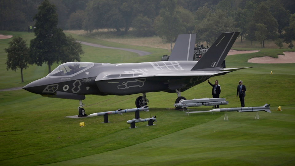 Men look at a demonstration F35 jet standing on display beside a golf course prior to a NATO summit at the Celtic Manor Resort in Newport, Wales, Wednesday, Sept. 3, 2014. (AP / Matt Dunham)