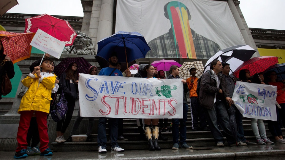 Students, including Michael Cheung, 9, far left, entering grade 5 at Lord Roberts Elementary School, attend a rally to show opposition to the teachers' strike in Vancouver, on Tuesday, Sept. 2, 2014. (Darryl Dyck / THE CANADIAN PRESS)