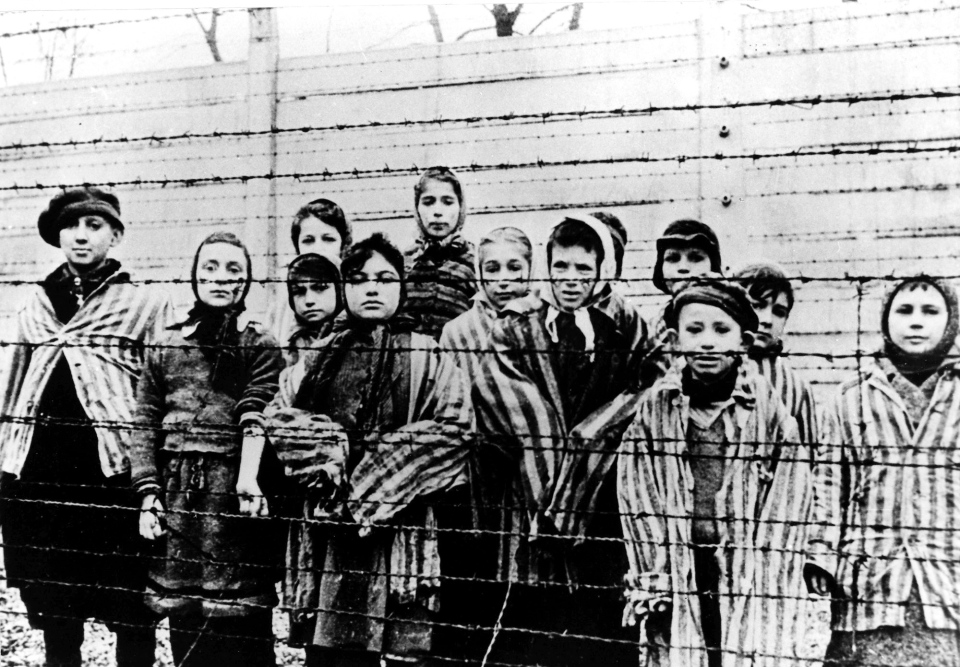 This file picture taken just after the liberation by the Soviet army in January, 1945 shows a group of children wearing concentration camp uniforms behind barbed wire fencing in the Oswiecim (Auschwitz) Nazi concentration camp.