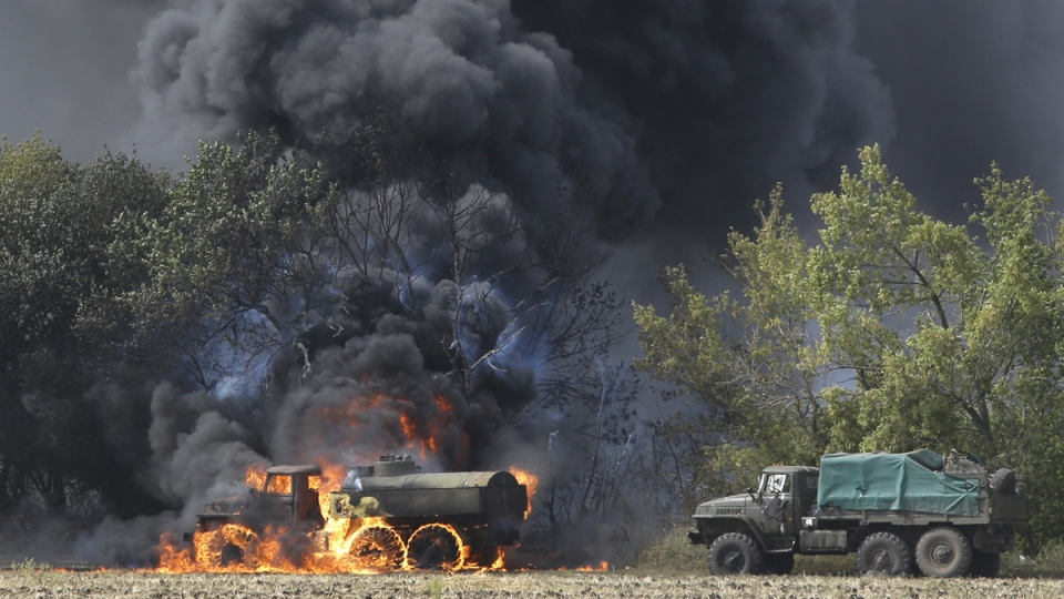 Unmarked military vehicles burn on a country road in the village of Berezove, eastern Ukraine, Thursday, Sept. 4, 2014. (AP / Sergei Grits)