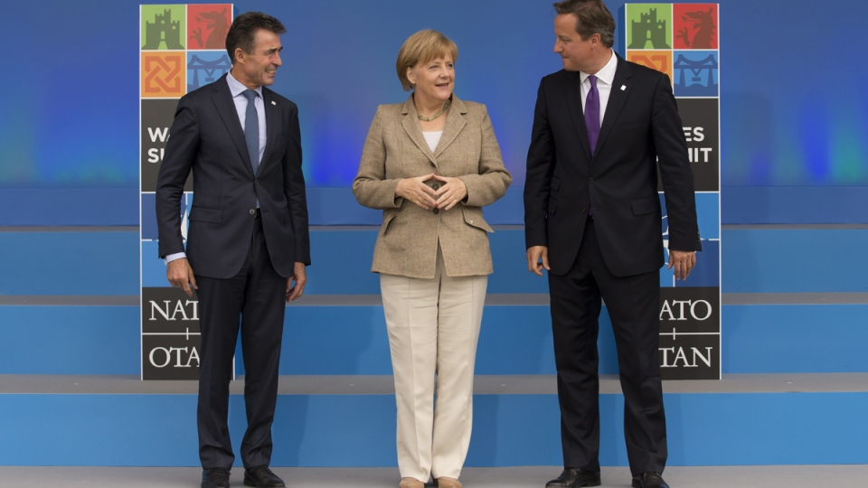 German Chancellor Angela Merkel, centre, stands with NATO Secretary General Anders Fogh Rasmussen, left, and British Prime Minister David Cameron as she arrives for the NATO summit at the Celtic Manor Resort in Newport, Wales on Thursday, Sept. 4, 2014. (AP / Jon Super)