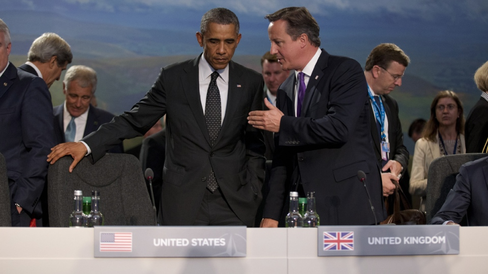 U.S. President Barack Obama and British Prime Minister David Cameron, right, speak before taking their seats at the start of a NATO-Afghanistan round table meeting during a NATO summit at the Celtic Manor Resort in Newport, Wales on Thursday, Sept. 4, 2014. (AP / Matt Dunham)
