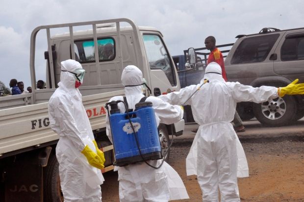 Health workers spray each other in Monrovia