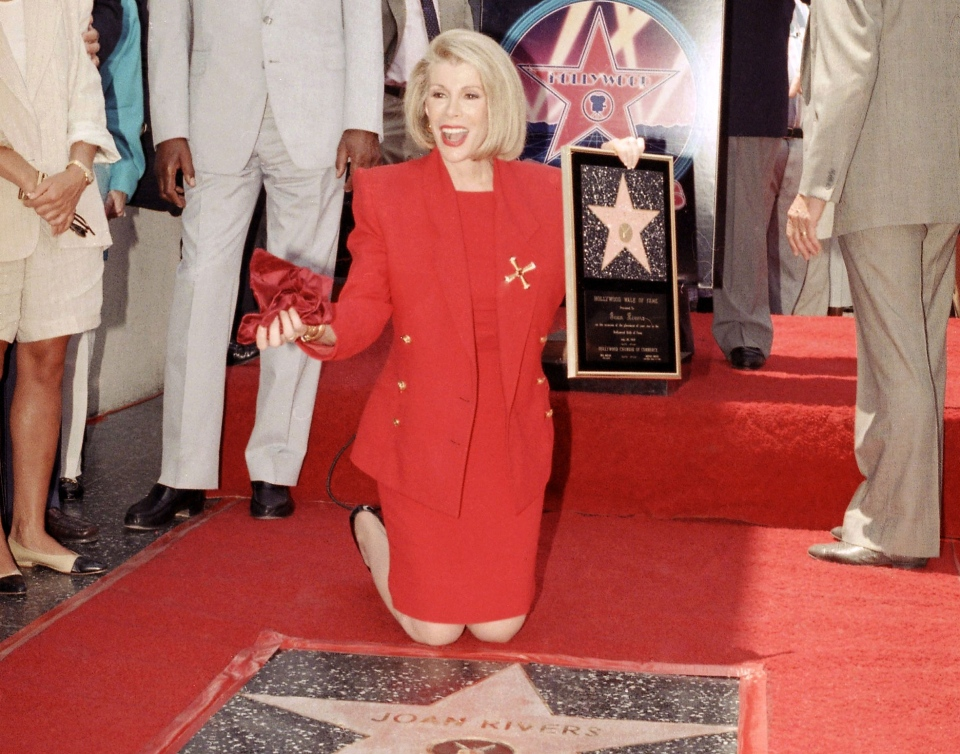 Joan Rivers poses next to her star on the Hollywood Walk of Fame during her induction ceremony in Los Angeles on July 26, 1989. (AP / Doug Sheridan)